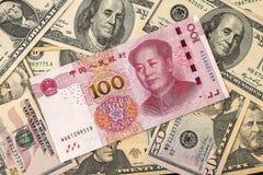 在美国美元背景的中国元钞票 免版税图库摄影
