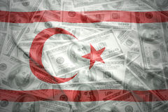 在美国美元金钱背景的挥动的北塞浦路斯旗子 库存照片