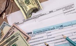 在美国1040报税表的被撕毁的美元 免版税库存照片