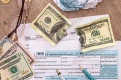 在美国1040报税表的被撕毁的美元 免版税库存图片