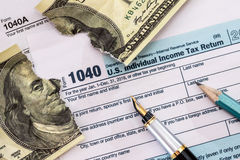 在美国1040报税表的被撕毁的美元 库存照片