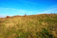 在美好的五颜六色的秋天象草的风景的看法在乡下 在小山的遥远的十字架 库存照片