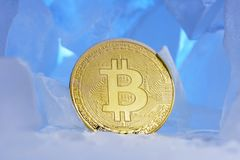 在美好的光的蓝色冰围拢的冻结的隐藏货币bitcoin面孔正面立场 库存照片