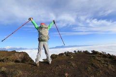 在美好的山峰的背包徒步旅行者远足者开放胳膊 图库摄影