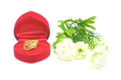 在美好的形状的金下垂有浮雕的贝壳花梢圆环首饰与在白色隔绝的花 免版税库存图片