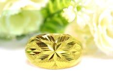 在美好的形状的金下垂有浮雕的贝壳花梢圆环首饰与在白色隔绝的花 免版税图库摄影