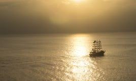 在美好的日落前面的船航行 免版税库存图片