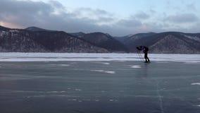 在美好的日落期间,人在冻贝加尔湖冰滑冰  影视素材