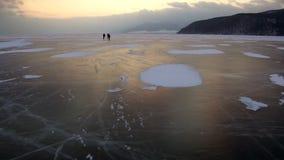 在美好的日落期间,人在冻贝加尔湖冰滑冰  股票视频