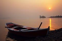 在美好的日落期间的一条小船 库存照片
