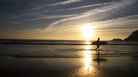 在美好的日落期间,冲浪者回家 免版税库存照片