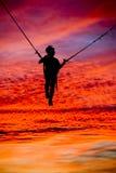 在美好的日落的Trampolining 库存照片