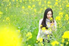 在美好的早期的春天,是最大的在上海在黄色强奸花中间的一个少妇立场归档了 免版税图库摄影