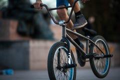 在美好的橙色bmx自行车男性爱好极端体育男性爱好低部特写镜头backgro的年轻少年自行车骑士男孩骑马 免版税图库摄影