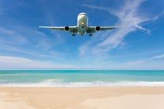 在美好的海滩和海背景上的飞机着陆 免版税库存图片