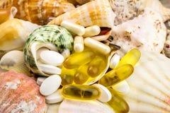 在美好的贝壳背景的混杂的自然食物补充药片 免版税库存照片