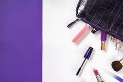 在美容师的化妆用品白色和紫罗兰色背景的 库存图片