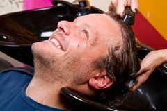 在美容院理发沙龙的洗涤的人头发 免版税库存照片