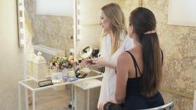在美容院的主要` s工作 化妆师组成他的客户,使用阴影很多调色板,不同 股票视频