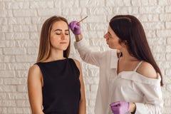 在美容院的眼眉女性顾客绘的主要美容师 库存照片