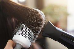 在美容院的美发师干燥妇女` s头发 库存照片