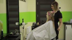 在美容院的美发师掠过的女孩` s头发 股票录像