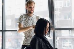 在美容院的美好的深色的妇女顾客笑,当谈话与年轻男性美发师时 做凉快 图库摄影