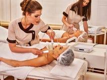 在美容院的面部按摩 电刺激夫妇护肤 免版税库存图片