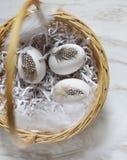 在羽毛篮子的3个白鸡蛋 免版税库存图片