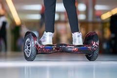 在翱翔委员会的女孩脚 自平衡的滑行车或微型segway 库存照片