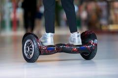 在翱翔委员会的女孩脚 自平衡的滑行车或微型segway 图库摄影