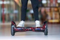 在翱翔委员会的女孩脚 自平衡的滑行车或微型segway 免版税图库摄影