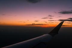 在翼的日落从在飞行期间的飞机窗口 免版税图库摄影
