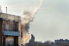 在老公寓顶楼上的火  卷曲从阳台的烟云 在年迈的房子和短小的被佩带的折衷接线 库存照片