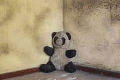 在老军事大厦的肮脏的被放弃的熊猫玩具 图库摄影