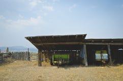 在老农场的老拖车在多灰尘的天空下 库存图片