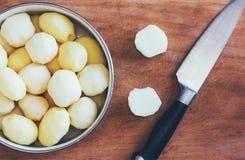 在老切板和厨刀特写镜头视图的未加工的被剥皮的土豆从上面 库存图片