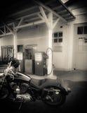 在老加油站前面的摩托车 免版税库存图片