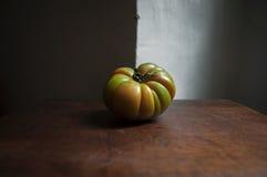 在老厨房用桌上的绿色和redish牛肉蕃茄 库存照片