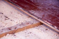在老台面厚木板下的锯木屑绝缘材料 免版税库存照片