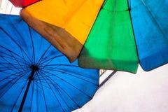 在老和肮脏的沙滩伞上色的生动多 库存照片