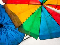 在老和肮脏的沙滩伞上色的生动多 库存图片