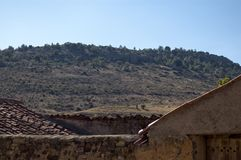 在老和被风化的屋顶之间的小山视图 免版税库存照片