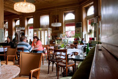 在老咖啡馆里面的人们与历史内部 免版税图库摄影