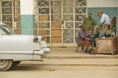 1955年在老商店前面的得到鞋子的卡迪拉克和战士在El林孔,古巴附近发光 免版税库存照片