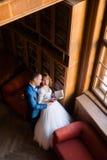 在老图书馆的典雅的婚礼夫妇 新娘和新郎常设witn在窗口附近预定 顶视图 免版税库存照片