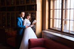 在老图书馆的典雅的婚礼夫妇 新娘和新郎常设witn在窗口附近预定 图库摄影