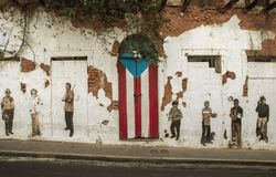 在老圣莒的门和波多黎各人旗子绘的街道画 免版税库存照片