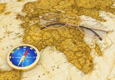 在老地图的金黄指南针与玻璃 免版税图库摄影