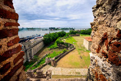 在老城市墙壁和圣多明哥新的工业港上的看法,通过堡垒-福特莱萨窗口  免版税库存照片
